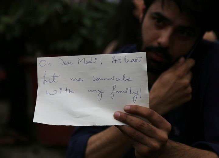 A Kashmiri, who works in Bangalore, holds a piece of paper addressing Prime Minister Narendra Modi during a protest against the government revoking Kashmir's special constitutional status in Bangalore, Aug. 5, 2019.