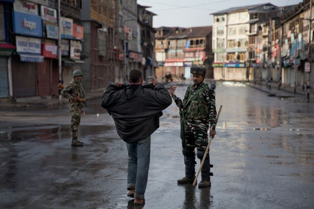 A paramilitary soldier orders a Kashmiri to lift his robe before frisking him during curfew in Srinagar,...
