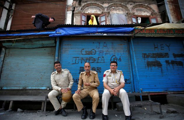 Policemen sit in front of closed shops during restrictions in Srinagar, August 6,