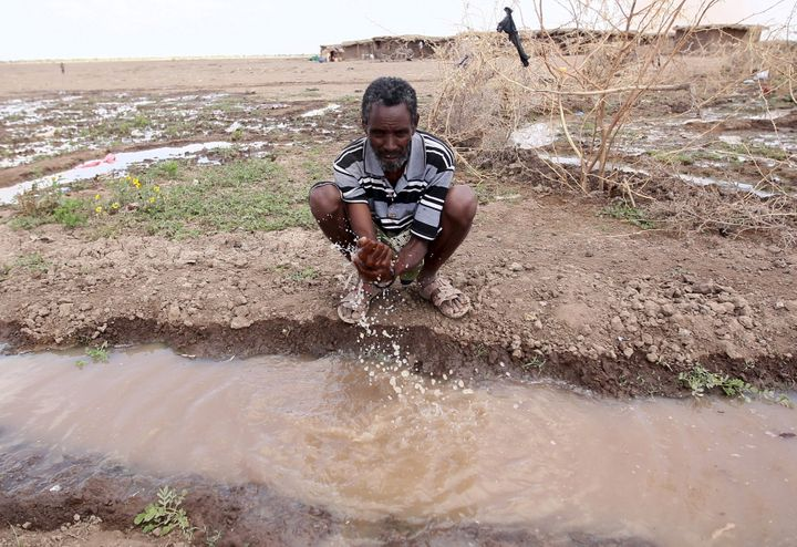 A man washes his hand in a trench in a drought-stricken region of Ethiopia in January 2016.