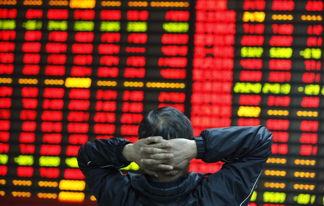 In this file photo, a trader watches stock prices at an exchange in Huaibei, China, April 10,