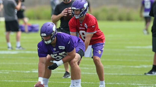 Minnesota Vikings quarterback Kirk Cousins, right, takes a snap from rookie center Garrett Bradbury during the NFL football team's training camp Friday, July 26, 2019, in Eagan, Minn. (AP Photo/Jim Mone)