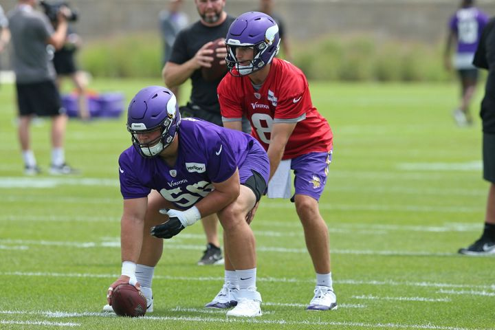 Minnesota Vikings quarterback Kirk Cousins takes a snap from rookie center Garrett Bradbury during a recent practice.