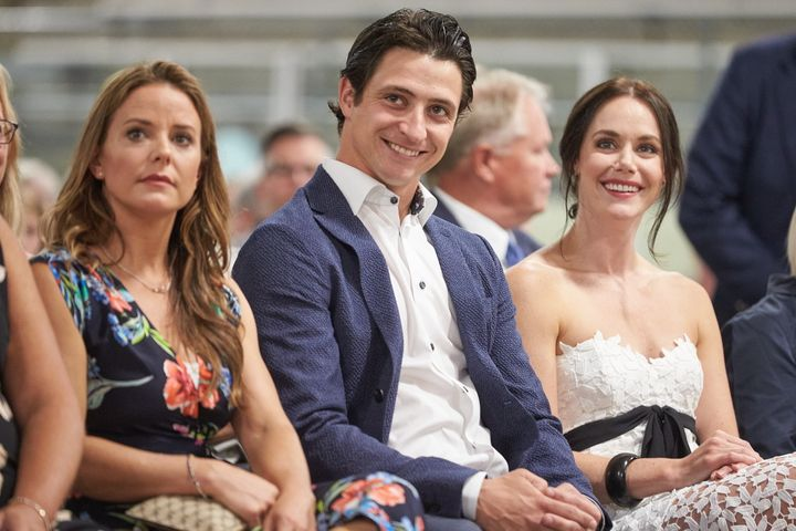 Scott Moir sits with his ice dance partner Tessa Virtue, right, and his fiancée Jackie Mascarin, left, during the ceremony for the unveiling of his Canada's Walk of Fame in Ilderton, Ont. on Aug. 7, 2019.