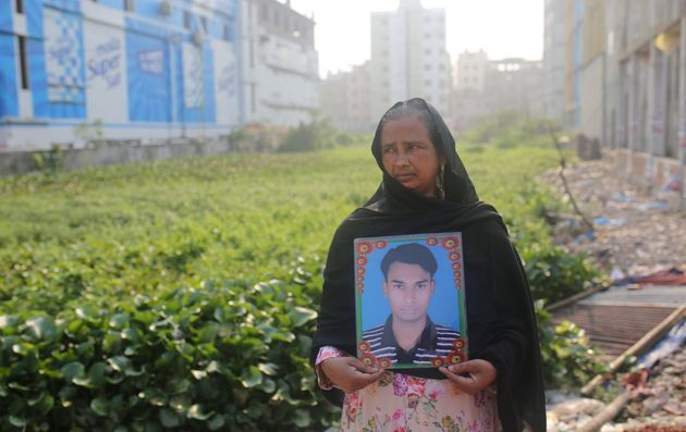 A woman holds a picture of a relative who went missing in the Rana Plaza building collapse, on the tragedy's...