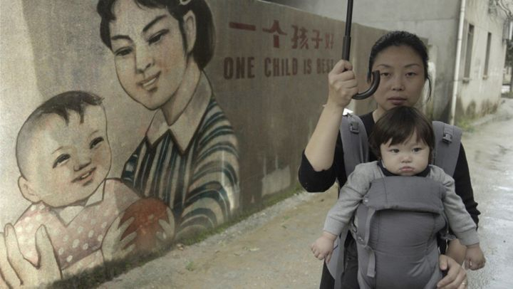 """""""One Child Nation"""" co-director Nanfu Wang and her son, next a propaganda mural promoting China's one-child policy."""