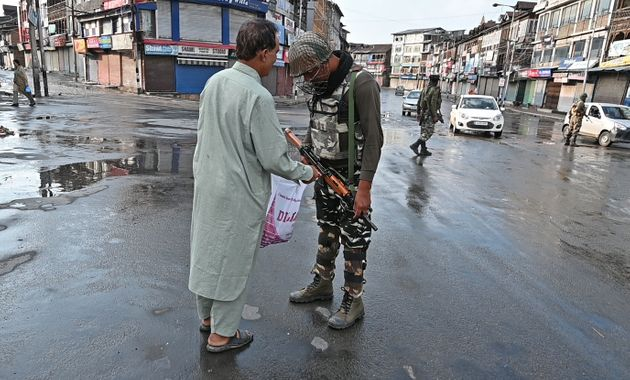 A security personnel checks the bag of a Kashmiri man during a curfew in Srinagar on August 8,