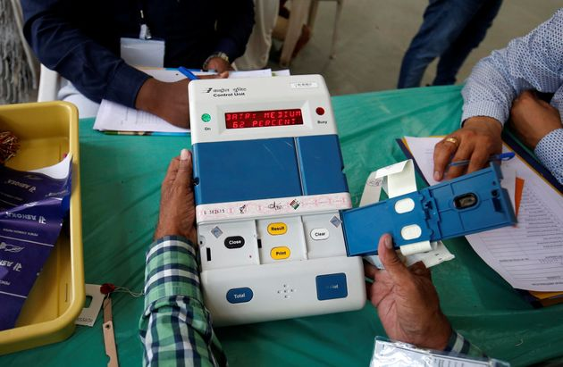 Election staff members open an electronic voting machine (EVM) to count votes inside a vote counting...