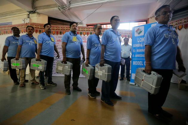 Election officials carry electronic voting machines for counting votes of in the general elections in...