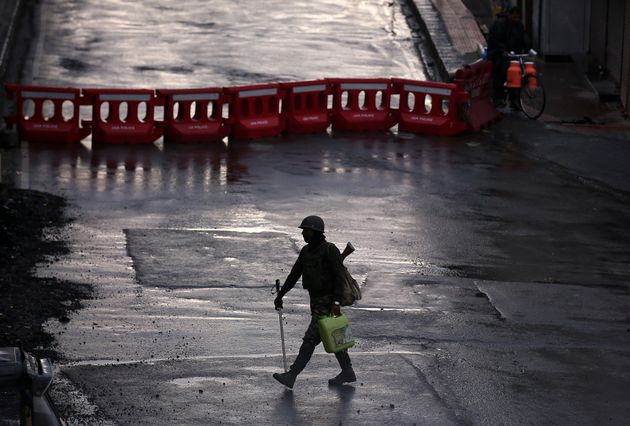 A security force personnel patrols a deserted road during restrictions after the government scrapped...