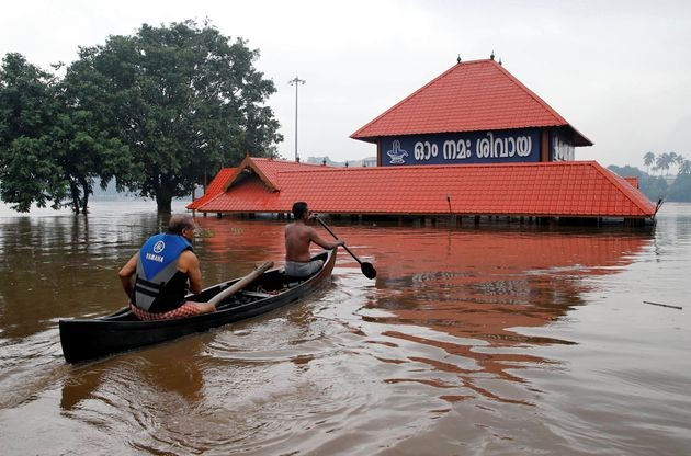 Members of a rescue team row a boat towards a submerged temple to look for a man believed to be stranded...