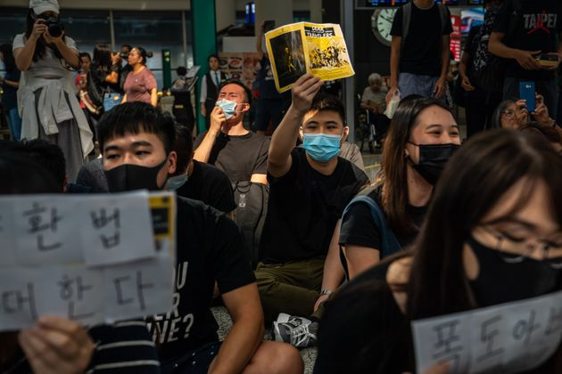 Protesters rally against a controversial extradition bill in the arrivals hall of Hong Kong's international...