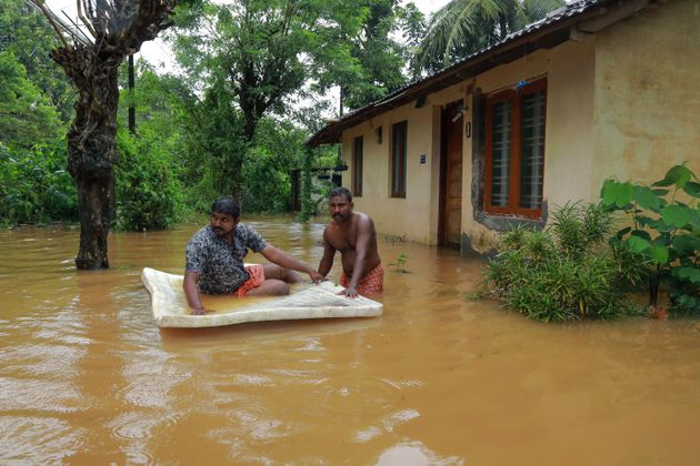 Men pass through flood waters at Eloor area in Ernakulam district,Kerala, on August 9,