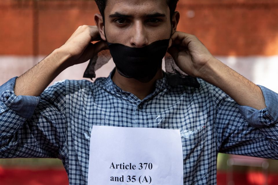 A Kashmiri man covers his mouth during a protest against the scrapping of the special constitutional...