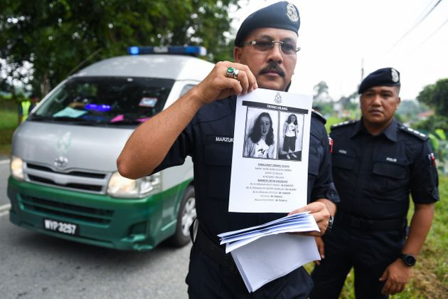 A Royal Malaysian Police officer holds a leaflet bearing a portrait of missing Nora at a