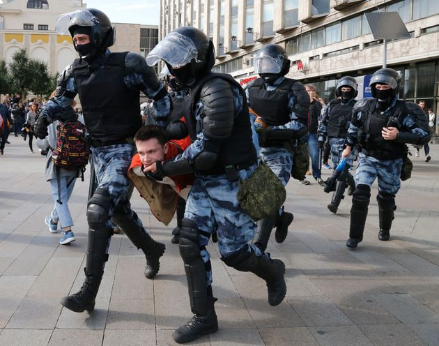 Police officers detain a protestor, during an unsanctioned rally in the centre of Moscow, Russia, Saturday,...