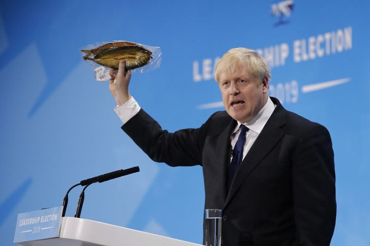 British Prime Minister Boris Johnson holds up a smoked kipper in plastic packaging.
