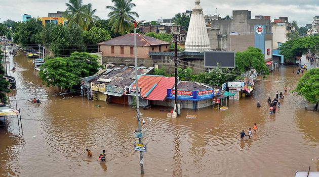 In this picture taken on August 6, 2019 people wade through a flood street in Sangli district of