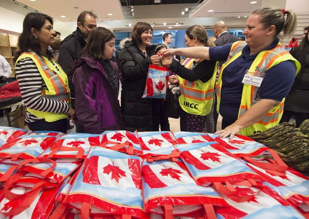 Then-newly-arrived Syrian refugee Anjilik Jaghlassian, centre, and her family receive winter clothes...