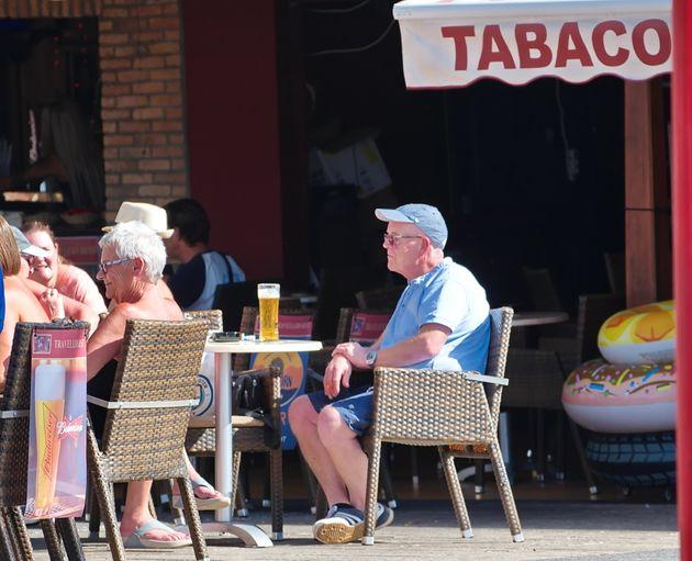 Un anciano británico toma una caña en una terraza
