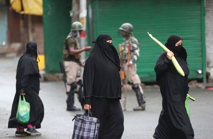 Kashmiri women holds bags filled with essentials and walk past Indian paramilitary soldiers closing off a street in Srinagar on Aug. 10, 2019.