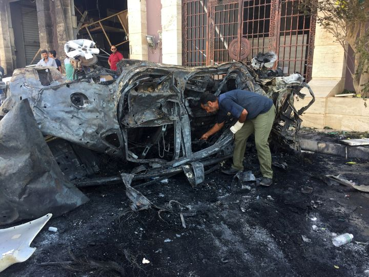 A security official inspects the site where a car bomb exploded in Benghazi, Libya August 10, 2019.