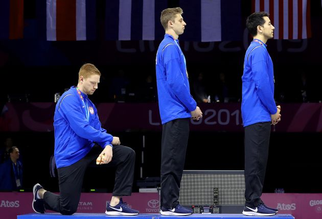 Gold medalist Race Imboden of United States takes a knee during the National Anthem Ceremony during the...