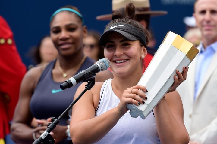 Bianca Andreescu holds the winner's trophy as Serena Williams looks on after Williams had to retire from the final of the Rogers Cup tennis tournament in Toronto on Aug. 11, 2019.
