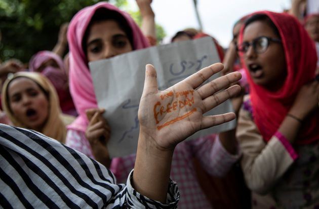 A Kashmiri woman shows her hand with a message as others shout slogans during a protest after the scrapping...