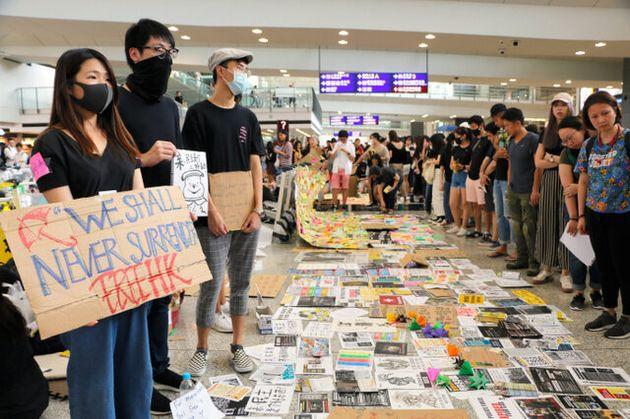 香港空港の到着ロビーで行われたデモで、「私たちは決して降伏しない」というメッセージを掲げる参加者。床には中国語、英語、日本語、ハングルなどで書かれたメッセージが並ぶ=2019年8月11日、西本秀撮影