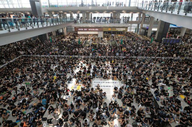 香港で12日、抗議の市民らが香港国際空港に集まり、座り込みを行った=AP