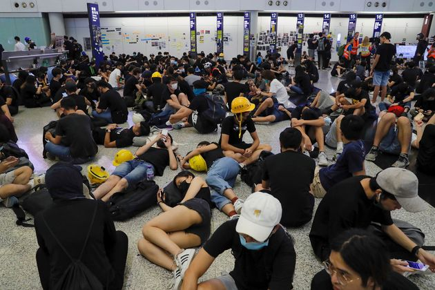 Protesters stage a sit-in protest at the Hong Kong International Airport, Monday, Aug. 12,