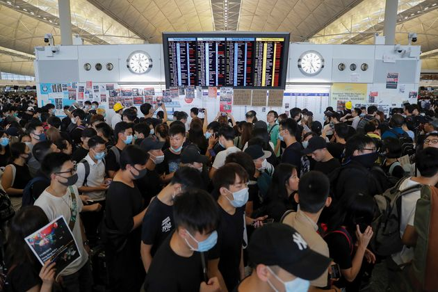 Protesters gather near a flights information board during a protest at the Hong Kong International Airport,...