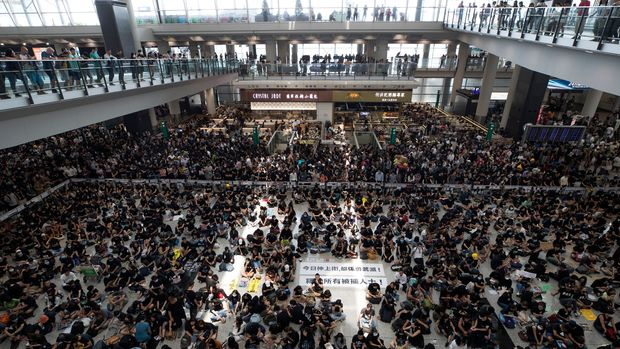 "Protesters surround banners that read ""Those charge to the street on today is brave!,"" center top, and ""Release all the detainees!"" during a sit-in rally at the arrival hall of the Hong Kong International airport in Hong Kong, Monday, Aug. 12, 2019. Hong Kong airport suspends check-in for all remaining flights Monday due to ongoing pro-democracy protest in terminal. (AP Photo/Vincent Thian)"