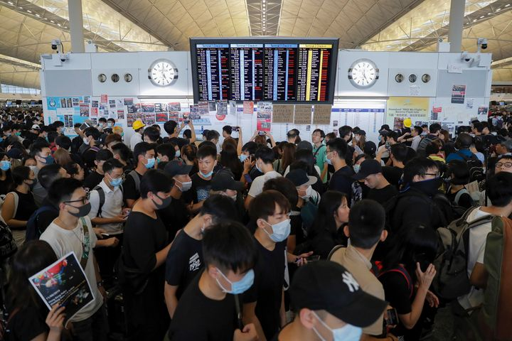 Protesters gather near a flights information board during a protest at the Hong Kong International Airport, Monday, Aug. 12,