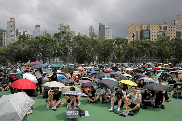 People holding umbrellas gather at Victoria Park to take part in an anti-extradition bill protest in...