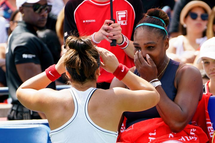 Bianca Andreescu left, sympathizes with Serena Williams, right background, after Williams retired from the Rogers Cup final on Sunday.