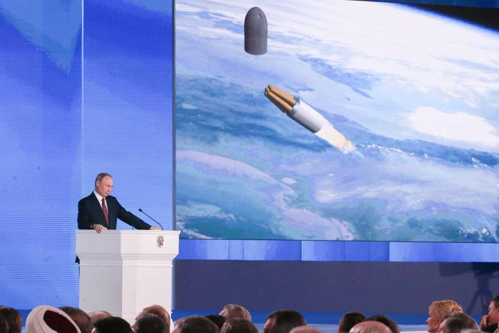 Russian President Vladimir Putin speaks in front of an animation of new nuclear missile technology in a 2018 address in Mosco
