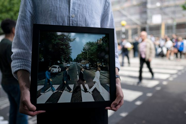 """A fan holds the cover of The Beatles' """"Abbey Road"""" outside Abbey Road Studios in London on Aug. 8, the 50th anniversary of the album's release."""