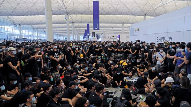 Protesters gather near an information board during a protest at the Hong Kong International Airport, Monday, Aug. 12, 2019. One of the world's busiest airports canceled all flights after thousands of Hong Kong pro-democracy protesters crowded into the main terminal Monday afternoon. (AP Photo/Kin Cheung)