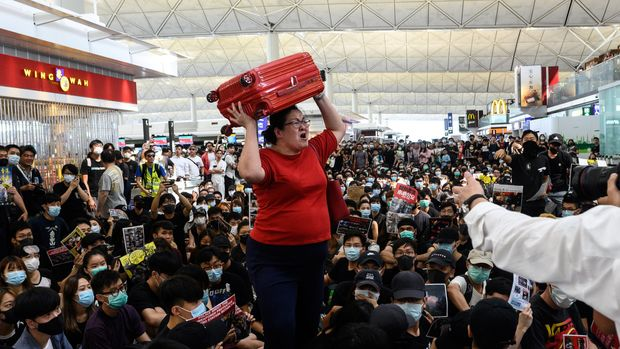 A traveller (C) shouts while holding her luggage as she tries to enter the departures gate area as Hong Kong pro-democracy protesters block access during another demonstration at Hong Kong's international airport on August 13, 2019. - Protesters blocked passengers at departure halls of Hong Kong airport on August 13, a day after a sit-in forced authorities to cancel all flights to and from the major international hub. (Photo by Philip FONG / AFP)        (Photo credit should read PHILIP FONG/AFP/Getty Images)