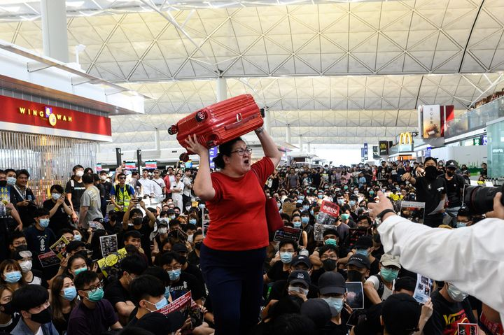 A traveller (C) shouts while holding her luggage as she tries to enter the departures gate area at Hong Kong's international