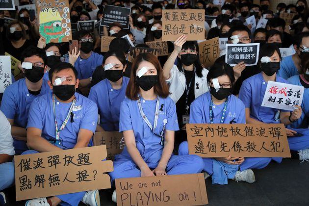 Medical staff stage a protest against police brutality on the protesters, at a hospital in Hong