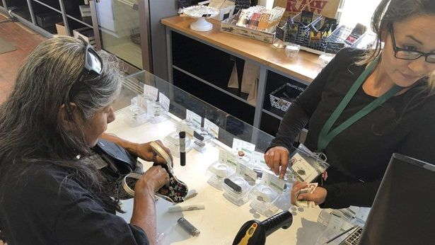 Tina Bernal, left, who uses cannabis to relieve chronic pain, buys a vial of marijuana at Minerva cannabis dispensary in New