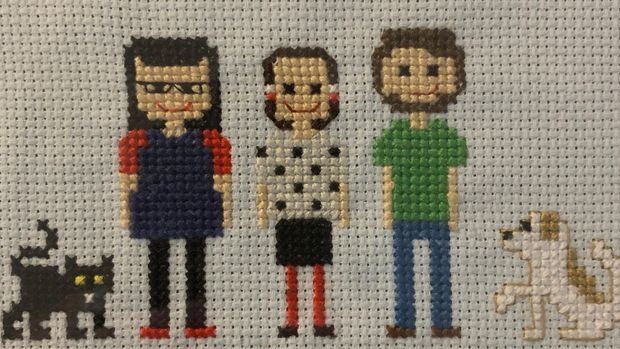 A cross stitch of the author, her best friend and her best friend's husband.