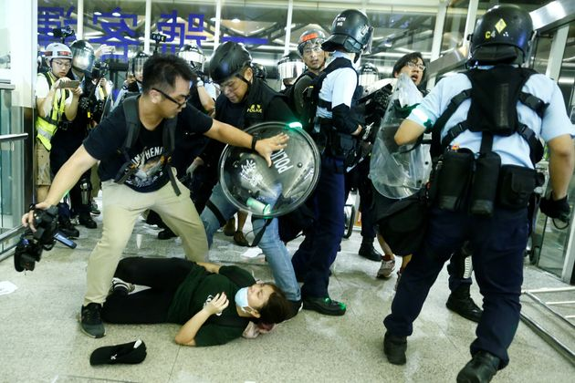Protesters and police clash at the entrance to the