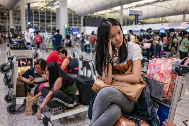 Stranded passengers sit near check-in counters as all flights have been cancelled after protesters occupied...