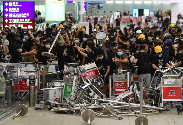 Pro-democracy protestors block the entrance to the airport terminals on August 13,