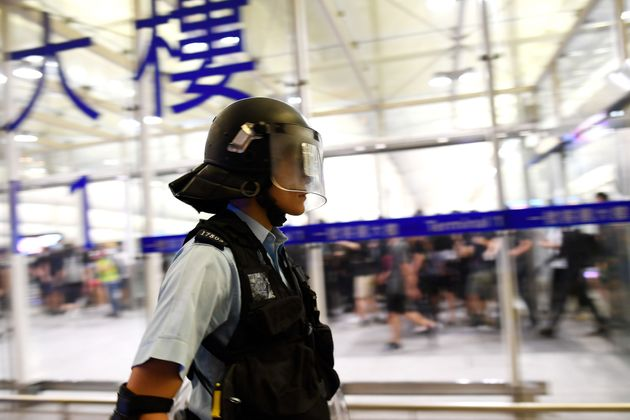 Riot police may their way through Hong Kong International Airport on Aug. 13,