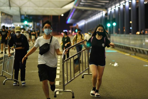 Pro-democracy protestors carry safety barriers to block the entrance to the airport terminals after a...
